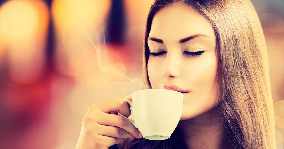 Hübsche Frau trinkt eine Tasse Kaffee.
