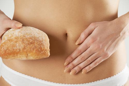 Frau hält Brot vor ihren Bauch